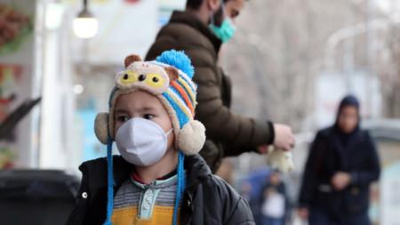 Дете със защитна маска в Техеран