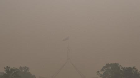 Австралийският флаг върху сградата на парламента в Канбера се вее, обгърнат от гъстия смог