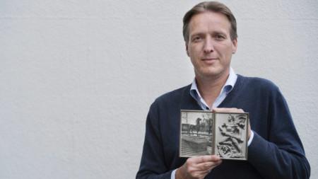 Артур Бранд със снимки на открити от него скулптури.