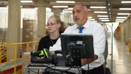 Премиерът кара мотокар при обиколката си в нов логистичен център край София.