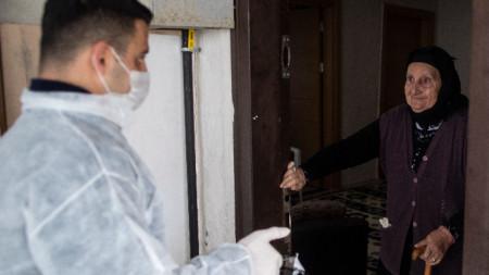 Служител на социалния патронаж в Истанбул доставя храна на възрастна жителка на мегаполиса, март 2020 г.