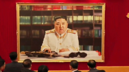 Делегати на конгреса на комунистическата партия в Пхенян проучват новия портрет на лидера Ким Чен-ун.