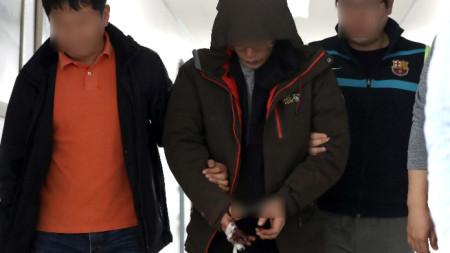 Полицаи ескортират 42-годишния подпалвач в полицейски участък в град Чинджу, Южна Корея.