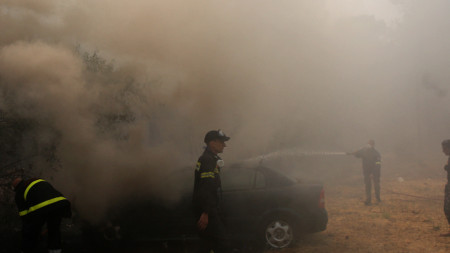 Пожарникари гасят горящ автомобил в района на Варибоби, предградие на Атина, 4 август 2021 г.