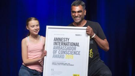 """Грета Тунберг позира с наградата, която ѝ бе връчена от генералния секретар на """"Амнести интернешънъл"""" Куми Найдо на церемония във Вашингтон."""