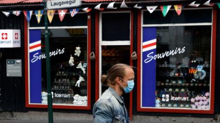 Мъж с маска пред магазин за сувенири в Рейкявик, столицата на Исландия.