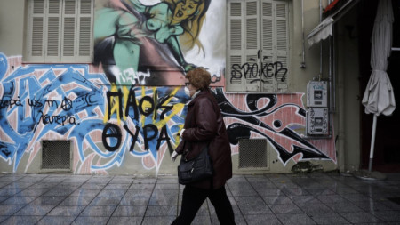 Възрастна жена с маска се разхожда в центъра на Солун.