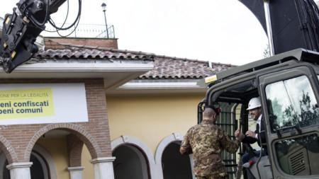 С бяла каска вътрешният министър Матео Салвини (вдясно) откърти парче от покрива на мафиотска вилата в Рим.