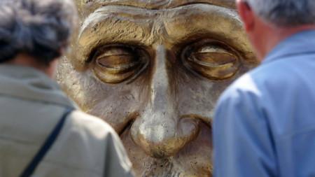 Възрастни румънци гледат скулптура на Робер Шуман в парк в Букурещ след откриването му през май 2006 г.
