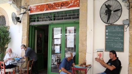 Келнер сервира кафе на клиент в заведение в Никозия.