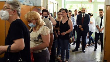 Премиерът реформатор Никол Пашинян (вторият от дясно на ляво) в изборна секция в Ереван.
