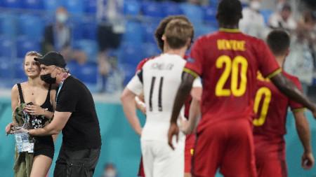 Футболистите на Белгия и Финландия гледат невярващо как жена нахлу на терена на стадиона в Санк Петербург и бе хваната от охраната