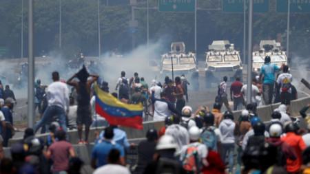 """Бронирани машини се насочват към бунтуващи се демонстранти пред ВВС базата """"Карлота"""" в Каракас."""