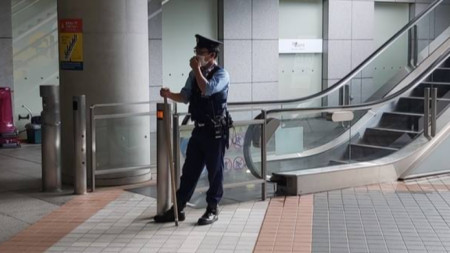 Полицай с пръчка бди до ескалатор.