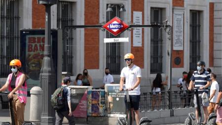 Туристи с електрически скутери пресичат площад Пуерта дел Сол в Мадрид, 3 август 2021 г.