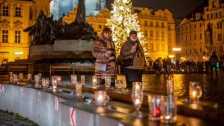 Жени вървят покрай наредени в знак на протест чаши за бира в центъра на Прага