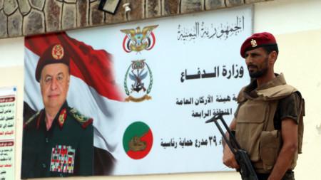 Войник на южните сепаратисти стои пред постер с лика на президентът Хади в Аден