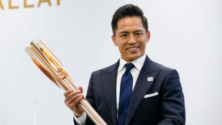 Трикратният олимпийски шампион в джудото Тадахиро Номура показва факела.