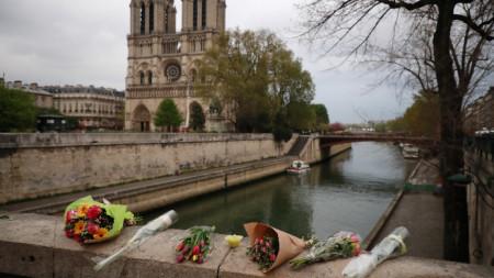 Оставени от туристи цветя в района на опожарената катедрала в Париж.