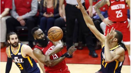 Хардън подава топката между двама баскетболисти на Юта.