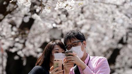 Японци със защитни маски си правят селфи на фона на цъфтящите вишни в парк в Токио -  22 март 2020 г.