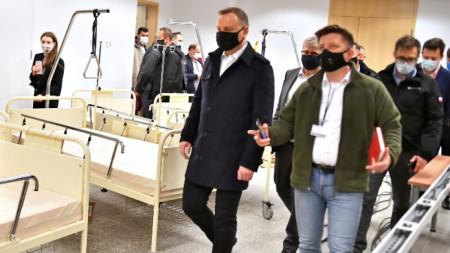 Президентът на Полша Анджей Дуда (вляво) по време на посещението си на Националния стадион във Варшава, където ще бъде разкрита болница за лечение на болни с коронавирус
