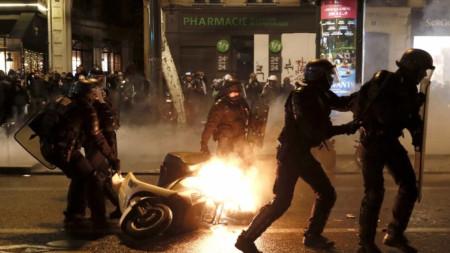 """Полицаи махат подпален скутер, след като в събота вечерта в Париж се стигна до сблъсъци между силите на реда и част от демонстриращите """"жълтите жилетки""""  в т.нар. """"жълта нощ""""."""