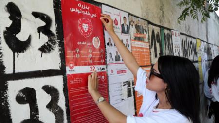 """Привърженичка на създадената през юни партия """"Калб Тунес"""" лепи предизборен плакат в град Бизерта, Северен Тунис."""