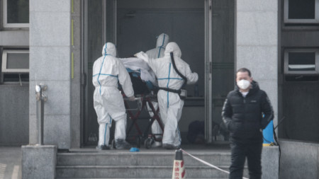 """Медицински екип вкарва пациент в болницата """"Цзининтан"""" в китайския град Ухан, където са настанени заразени с новия вирус."""