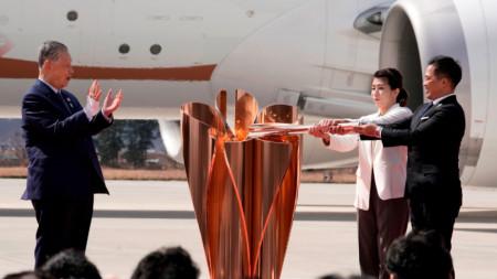 Олимпийските шампиони по борба Саори Йошида (с бялото сако) и по джудо Тадахиро Номура палят огъня в жертвеника.