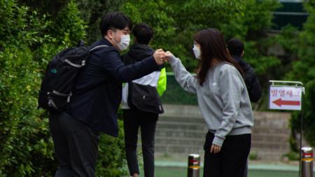 Ученик и учителка в гимназия в Сеул се поздравяват на влизане в учебното заведение, 20 май 2020 г.