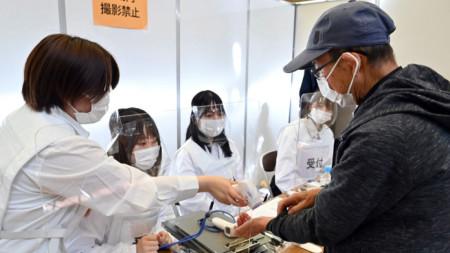 Проверка на температурата преди ваксинация в Токио.