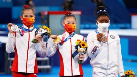 Байлс (вдясно) покзва бронза си в компанията на шампионката Гуан и Тан от Китай.