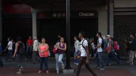 Жители на Каракас чакат автобус, след като авария с тока спря движението на метрото.