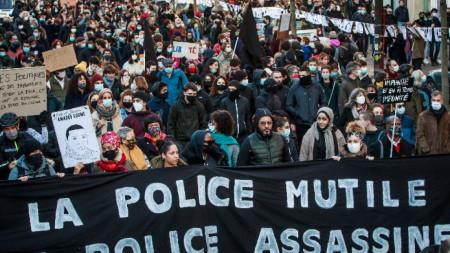 """Протестиращи държат транспарант с надпис """"Полицията осакатява, полицията убива"""" по време на демонстрация срещу новия спорен Закон за глобалната сигурност, Париж, 28 ноември 2020 г."""