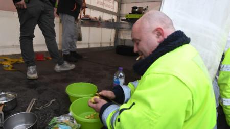 Шофьор на камион приготвя импровизирана вечеря близо до входа на пристанище Дувър, 23 декември 2020 г.