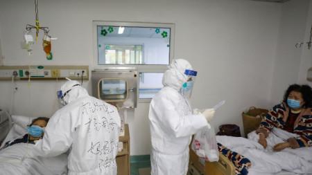 Лекари помагат на заразени с новия коронавирус в болница в Ухан