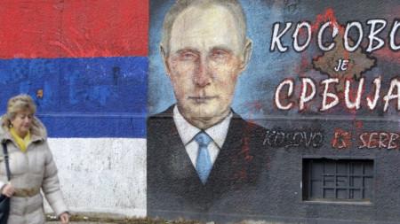 """Жена минава край изрисунав портрет на Владимир Путин и надпис """"Косово е Сърбия"""" в Белград. Сръбските власти готвят топло посрещане на руския президент за визитата му."""
