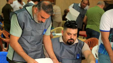 Служители на Независимата висша избирателна комисия (IHEC) броят гласовете на парламентарните избори в Ирак, Багдад, 13 октомври 2021 г.
