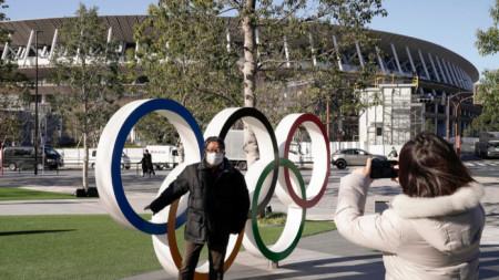 Турист се снима пред олимпийските кръгове в Токио. Все по-малко вероятно изглежда провеждането на Игрите тази година.