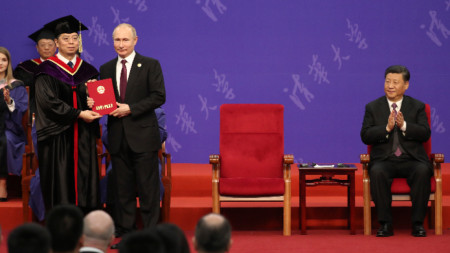 Владимир Путин получава удостоверение за доктор хонорис кауза на Пекинския университет Цинхуа под аплодисментите на Си Цзинпин (вдясно).