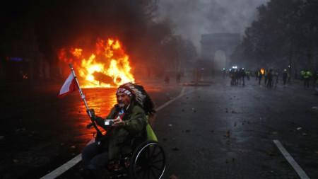 Горяща кола на фона на Триумфалната арка в Париж при сблъсъци на полицията и и протестиращи в събота привечер.