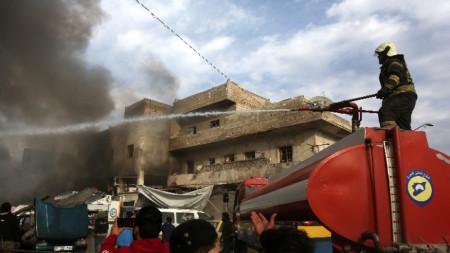 Пожарникари се опитват да потушат пожар след ракетна атака в източната част на Идлиб.