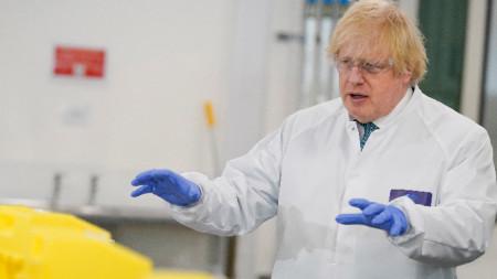 Британският премиер Борис Джонсън с предпазно облекло