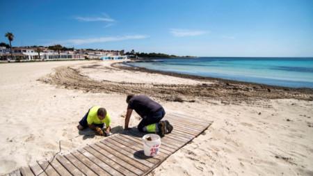 Работници подготвят плаж на испанския остров Менорка в очакване на решение за отварянето му за посетители.