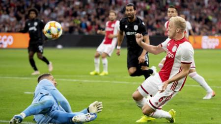 Халфът на Аякс Ван де Беек се опитва да преодолее вратаря на ПАОК Паскалаки.