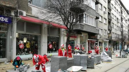 "Работници, облечени като Дядо Коледа, редят плочки по столичната улица ""Граф Игнатиев""."