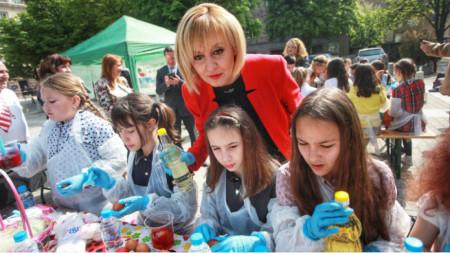 Маја Манолова и деца која на тргу фарбају јаја