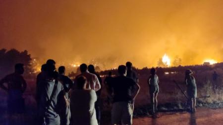 Жители наблюдават горския пожар на гръцкия остров Евия.