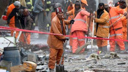 Афганистански служители разчистват след талибанския атентат с линейка бомба в Кабул миналата седмица, убил над 100 души и ранил над 200.